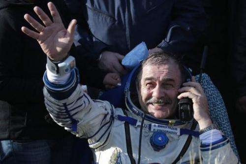 Russian cosmonaut Pavel Vinogradov waves shortly after landing in Kazakhstan on September 11, 2013