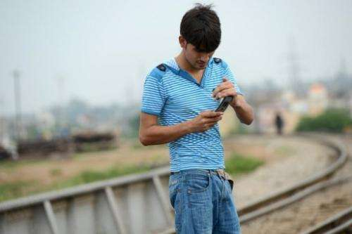 A man checks his messages alongside a railway track in Rawalpindi on September 10, 2013
