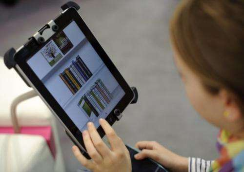 A woman tries out an eBook reader app on an Apple iPad at the Leipzig Book Fair on March 15, 2012