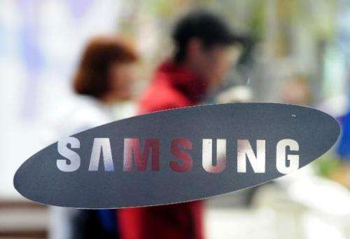 South Koreans walk past a Samsung logo in Seoul on April 22, 2011
