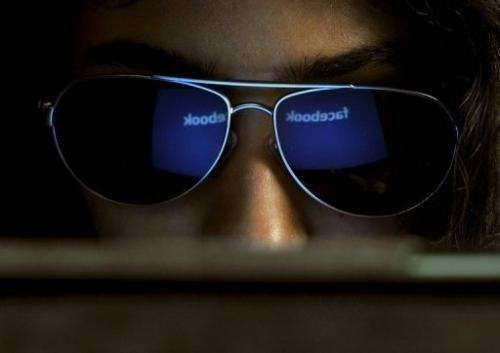 The 'Facebook' logo is reflected in a young woman's sunglasses as she browses the Internet in Bangalore, on May 15, 2012
