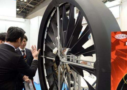Visitors look at KISCO's Tam Turbine wind power generator during the PV Expo in Tokyo, on February 27, 2013