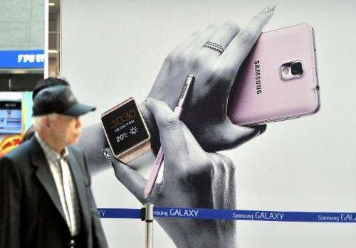 Pedestrians walk past a sign board advertising Samsung Electronics' Galaxy Note 3 smartphone at a railway station in Seoul on Oc
