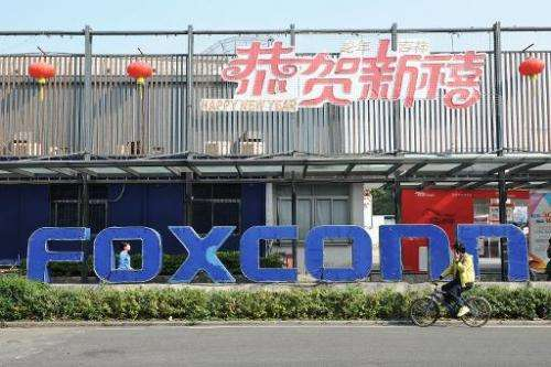 People walk past a Foxconn recruitment point in Shenzhen, south China's Guangdong province, on February 22, 2013