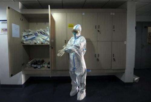A Beijing Center of Disease Control staff member puts on a decontamination suit in their office in Beijing