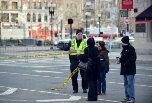 A Boston police officer speaks to passersby outside the Fairmont Copley Plaza Hotel on April 16, 2013 in Boston