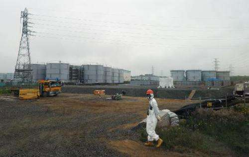 A construction worker walks near water tanks at the Fukushima nuclear plant in Fukushima prefecture, Japan on June 12, 2013