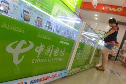 A customer selects mobile phones at a China Telecom store in Wuhan, in central China's Hubei province on August 21, 2013