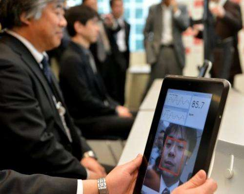 A Fujitsu engineer demonstrates how a smartphone that can take the pulse of a user works, on March 18, 2013