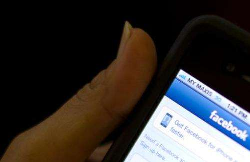 A girl logs into Facebook on her smartphone in Kuala Lumpur on May 15, 2012