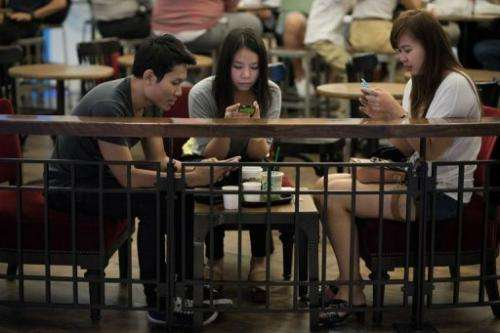 A group of friends look at their smartphones at a coffee shop in Bangkok on March 19, 2013