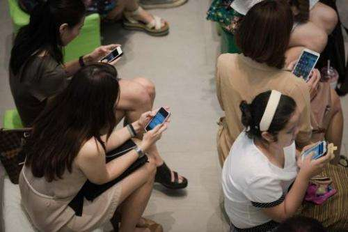 A group of people use their smartphones at a shopping mall in Bangkok, March 21, 2013
