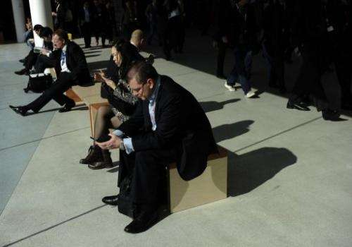 A man checks a mobile phone at the 2013 Mobile World Congress in Barcelona on February 26, 2013