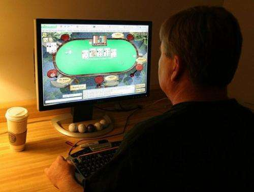 A man plays poker on an Internet gaming site from his home in Manassas, Virginia on October 2, 2006