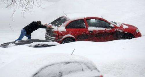 A man pushes a jammed car as heavy snow falls in Moscow, on March 15, 2013