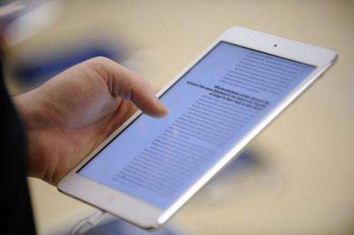 A man reads on a new iPad mini during the opening of a new Apple store in Saint-Herblain on November 15, 2012