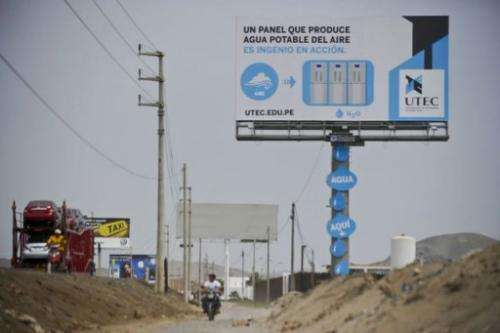 A man rides a motorbike past a billboard used to turn humidity into drinkable water in Bujama, March 15, 2013