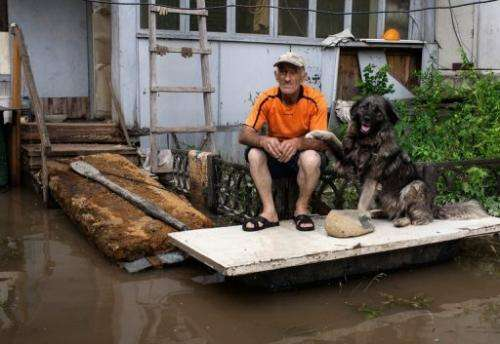 A man sits with his dog on his porch in Krasnaya Rechka near Khabarovsk in Russia's Amur region on August 22, 2013.