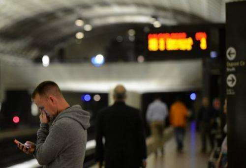 A man uses his smartphone in a metro station in Washington, DC on May 9, 2012