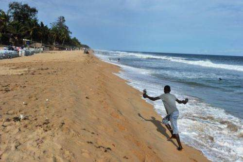 A man walks on the beach of Grand-Bassam, a town 40 km east of Abidjan threatened by coastal erosion, on May 17, 2012