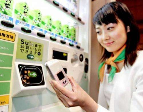 A model shows how to use a mobile phone equipped with a smartcard chip to pay a vending machine in Tokyo, 11 July 2005
