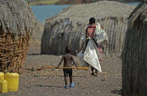 A mother and child walk in the village of Komote on the shores of Lake Turkana, northern Kenya on May 18, 2012