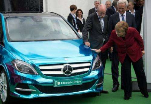 Angela Merkel (R) looks at a Mercedes E-drive electric car during the Electric Mobility conference on May 27, 2013