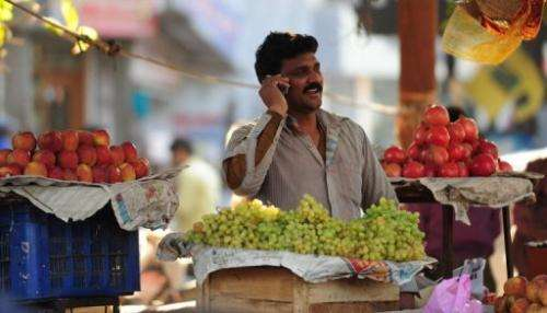 An Indian fruit vendor speaks on his mobile phone at a market in Allahabad on February 28, 2013