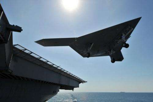 An X-47B unmanned combat air system demonstrator conducts a landing on May 17, 2013 on a deck in the Atlantic Ocean