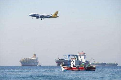 A plane flies over men from La Linea de La Concepcion fishing on August 16, 2013 near Gibraltar