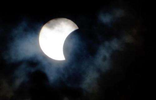A rare hybrid solar eclipse is seen through clouds from the Canary Island of Tenerife on November 3, 2013