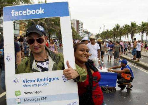 A reveller fancy dressed as a Facebook profile joins the Banda de Ipanama carnival street band as they parade along Ipanema beac