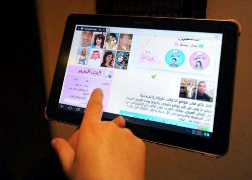 A Saudi woman uses a tablet computer to visit a website offering a matchmaking service for people hoping to get married
