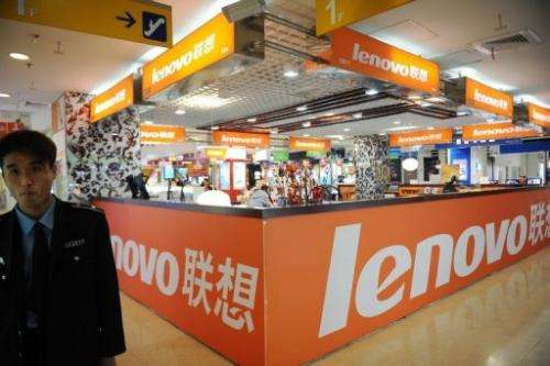 A security guard walks past a Lenovo shop in a computer mall in Beijing on November 3, 2011