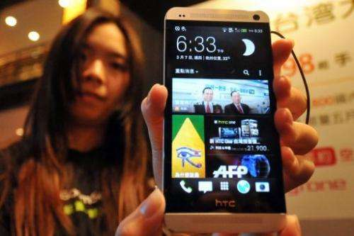 A staff member displays smartphone maker HTC's new 'HTC One' during a press conference in Taipei on March 7, 2013