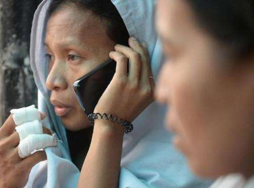 A survivor (left) talks to a relative over a borrowed mobile phone in Cebu City, central Philippines, on August 17, 2013 after a