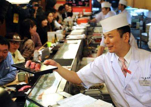A sushi chef serves up tuna sushi made from a bluefin tuna at a popular Japanese chain near Tokyo's Tsukiji fish market on Janua
