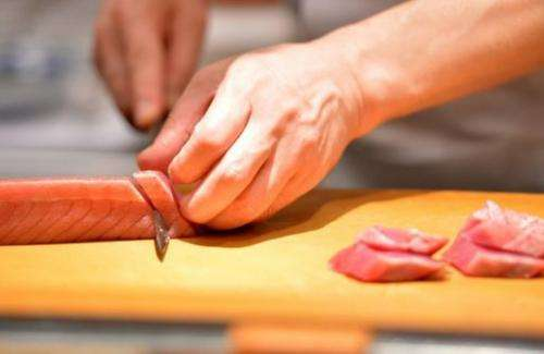A sushi chef slices up tuna at a restaurant in Tokyo on July 16, 2013