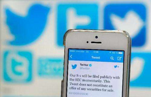 A Twitter tweet announcing the company's planned initial public offering (IPO) is pictured on a mobile telephone back-dropped by