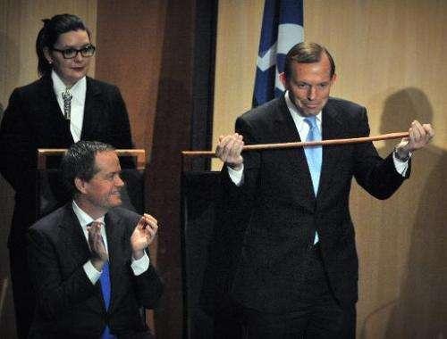 Australian Opposition Leader Bill Shorten (L) congratulates Prime Minister Tony Abbott (R) on the receipt of an Aboriginal fight