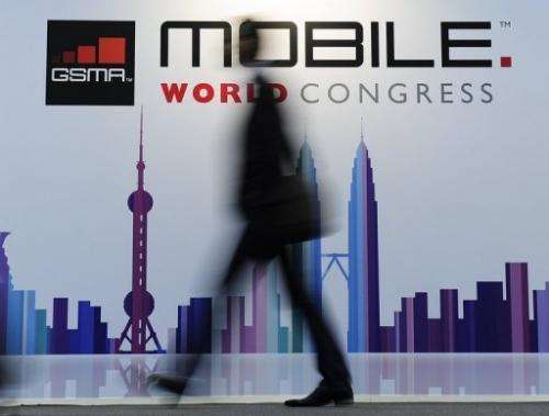A visitor walks past a board for the Mobile World Congress, in Barcelona, on February 25, 2013