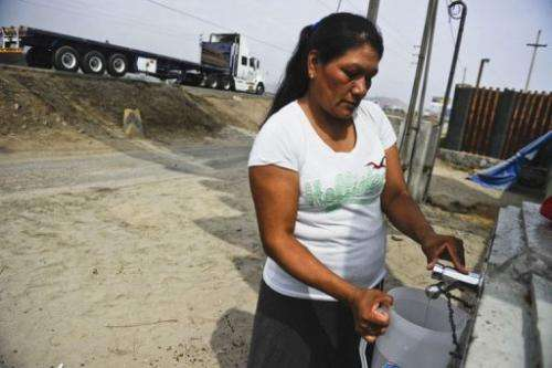 A woman fills a jug with water collected by a billboard 'dehumidifier' in Bujama,  south of Lima, on March 15, 2013