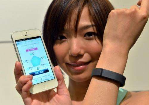 A woman models a Fitbit Flex wristband in Tokyo on May 7, 2013