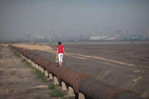 A woman standing on the banks of a 'toxic lake' surrounded by rare earth refineries near the inner Mongolian city of Baotou on A