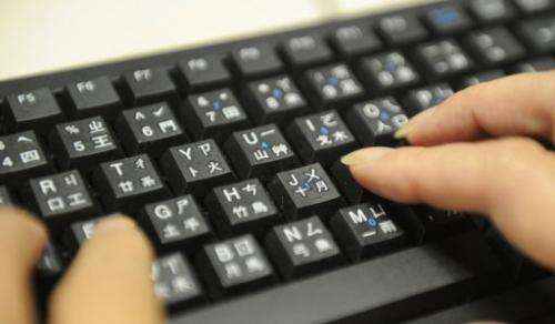 A woman uses a keyboard with keys illustrating both Roman letters and parts of Chinese charactures on August 27, 2010