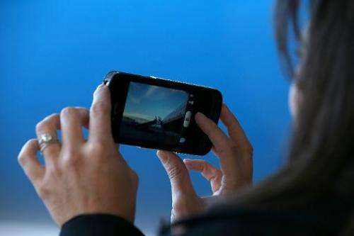 A woman watches a video on an iPhone as her plane lands at Denver International Airport in Denver, Colorado on October 23, 2012