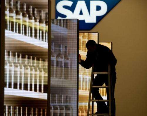 A worker adjusts screens at the stand of German software company SAP, prior to an IT fair in Hanover, on March 5, 2012
