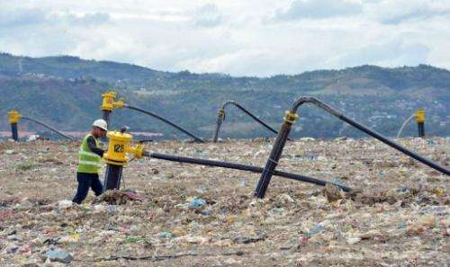 A worker inspects gas wells erected at the top of a dump site in Payatas village, Quezon City, February 21, 2013