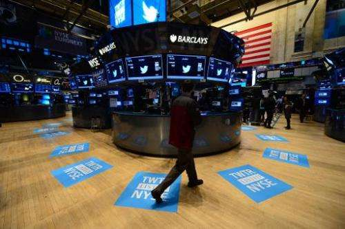 A worker stands walks near floor mats bearing the logo of Twitter and the company's TWTR stock symbol at the New York Stock Exch