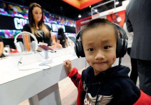 A young boy listens to music on a pair of headphones at the CES in Las Vegas on January 9, 2013